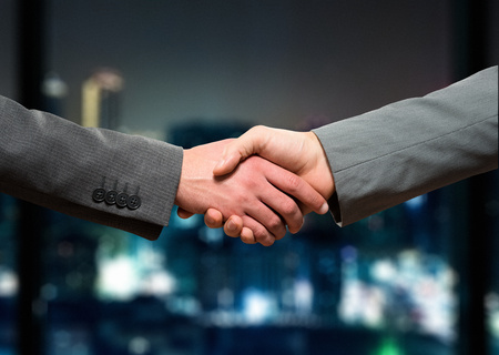 Businessmen shaking their hands at night Stock Photo
