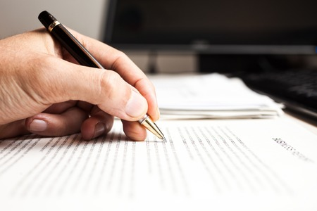 person writing: Close-up of a person writing on a document