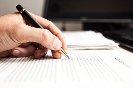 persona escribiendo: Primer plano de una persona que escribe en un documento