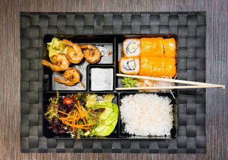 bento: Bento box with salad, maki, shrimps and rice