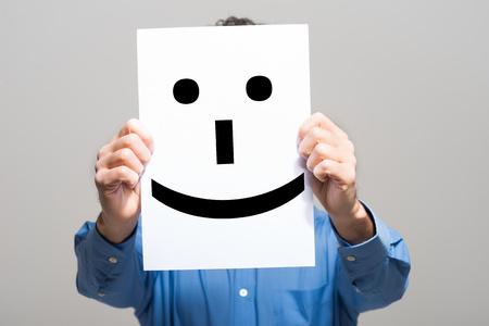 Hombre que sostiene un emoticono sonriente cara Foto de archivo - 55331192