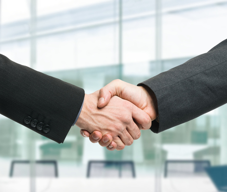 company job: Businessmen shaking hands to seal a deal Stock Photo
