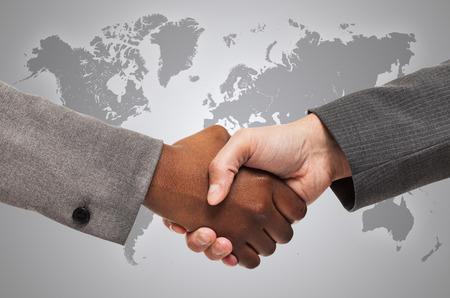 Handdruk tussen witte en zwarte mensen uit het bedrijfsleven
