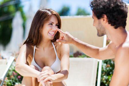 hombres guapos: Hombre que aplica la pantalla de sol en la nariz de su novia Foto de archivo