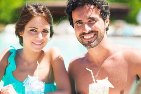 traje de bano: Joven pareja beber un c�ctel en la piscina