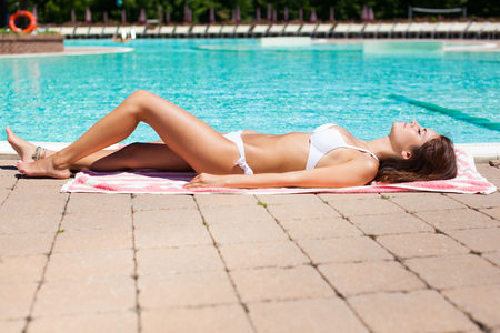Beautiful woman relaxing in a pool in summer Stock Photo
