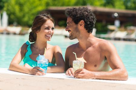 traje de bano: Retrato de una hermosa joven pareja disfrutando de un c�ctel en la piscina