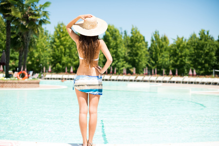 pareo: Woman holding her hat in front of a pool
