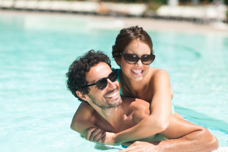 プールで楽しいを持っている若いカップル