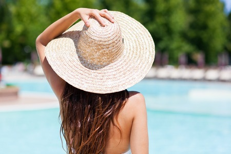 Woman holding her hat on the poolside Banque d'images