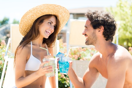 drink water: Smiling couple enjoying a cocktail while sitting on beach chairs Stock Photo