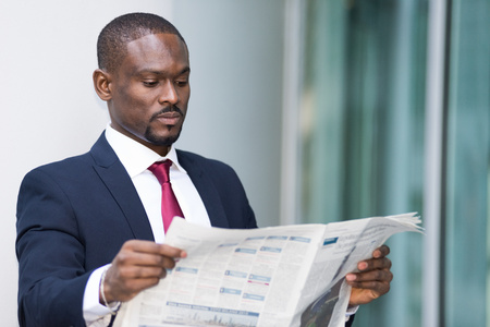 american banker: Portrait of a businessman reading a newspaper