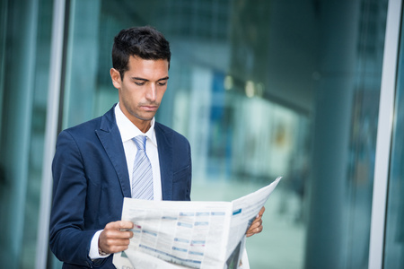 article of clothing: Portrait of a businessman reading a newspaper