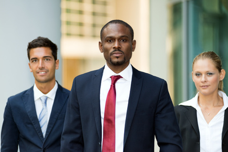 multiple ethnicity: Portrait of an african businessman in front of his team