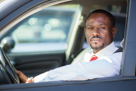 new motor vehicles: Black guy driving a car Stock Photo