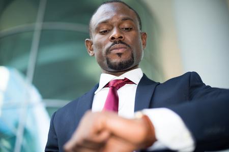 obrero trabajando: Apuesto hombre de negocios que buscan a su reloj