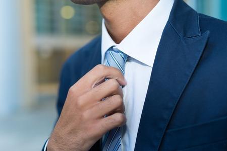 adjusting: Detail of a businessman adjusting his necktie Stock Photo