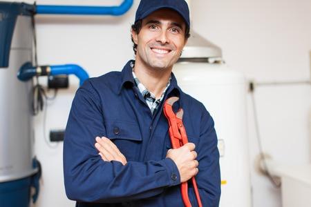 maintenance fitter: Smiling technician repairing an hot-water heater Stock Photo