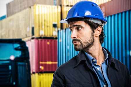 consign: Portrait of a worker in front of a stack of containers