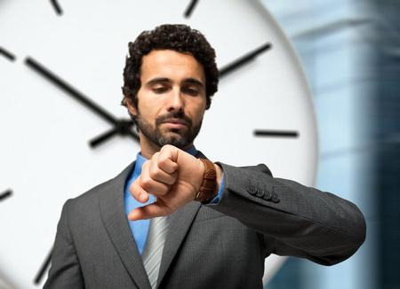 punctual: Mirando su reloj de hombre de negocios