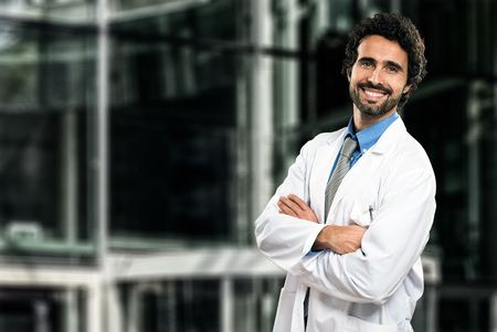 doctoring: Portrait of an handsome smiling doctor