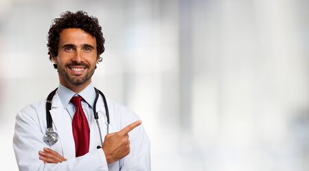doctoring: Portrait of a smiling doctor pointing his finger