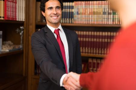 Portret van een glimlachende zakenman die een handdruk geeft aan een klant