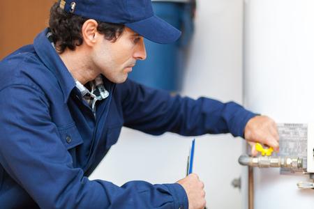 service man: Plumber repairing an hot-water heater Stock Photo