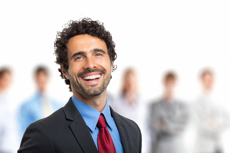 coworker: Team leader stands with coworkers in background