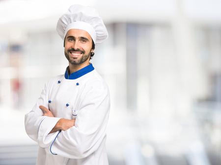 Portret van een glimlachende chef-kok voor een heldere achtergrond Stockfoto