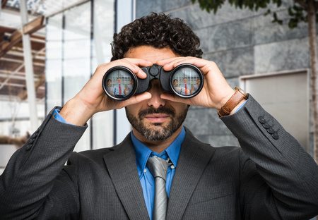 Portrait of a businessman using binoculars, people portraits reflected in the lens Stock Photo