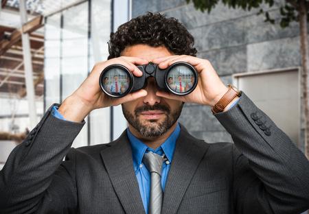Retrato de un hombre de negocios usando binoculares, retratos gente refleja en la lente Foto de archivo