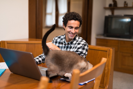 telecommuting: Portrait of a man caressing his cat while working at home Stock Photo
