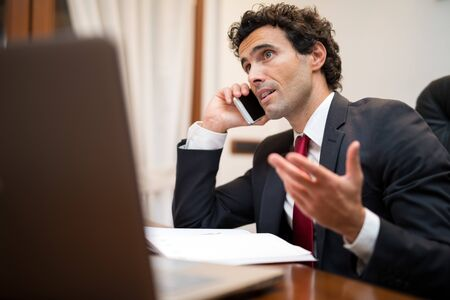 hablando por telefono: Retrato de un apuesto hombre de negocios hablando por teléfono