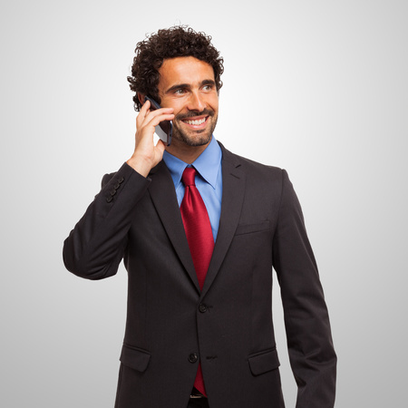 businessman phone: Portrait of an handsome young businessman talking on the phone Stock Photo
