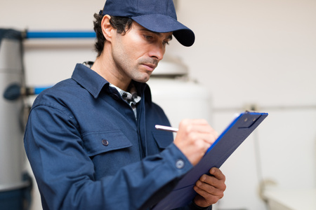 house inspection: Technician fixing an hot-water heater