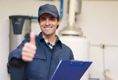 Sonriendo técnico de servicio a un calentador de agua Foto de archivo - 55653698