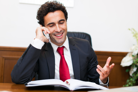 answering phone: Cheerful man in office answering the phone