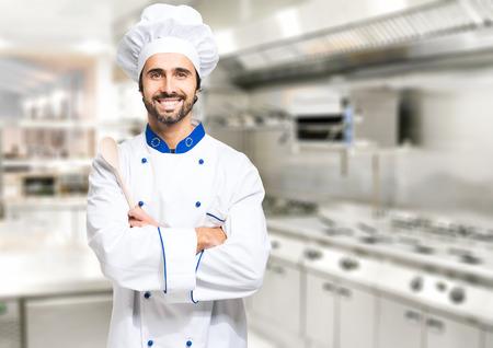 Glimlachende chef-kok in zijn keuken