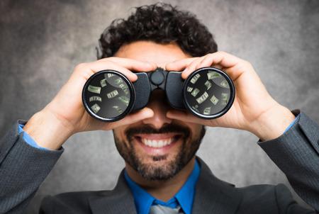 conclusion: El hombre de negocios usando binoculares, dinero refleja en la lente Foto de archivo