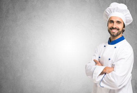 Smiling chef in front of a blank wall. Lots of copyspace