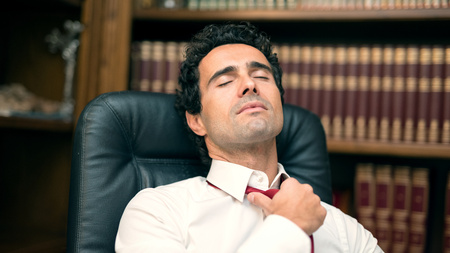 hard day at the office: Businessman loosing his necktie after an hard working day
