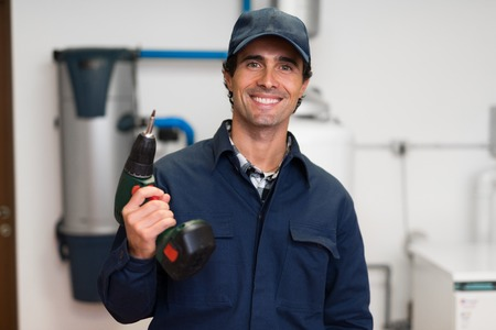 cordless: Smiling worker holding a cordless screwdriver Stock Photo