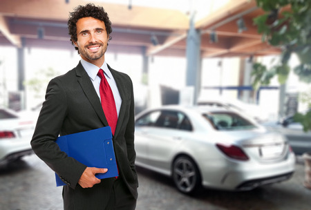 selling service: Salesman in a car showroom