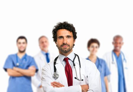 Portrait of a smiling doctor in front of his medical team photo