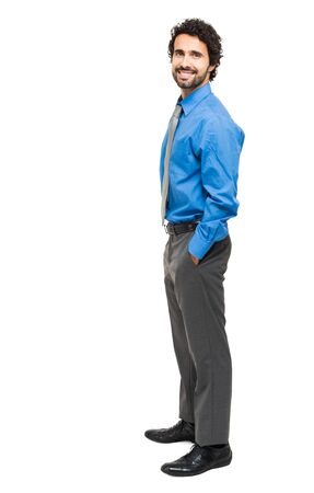 standing businessman: Full length portrait of a young businessman standing with his hands in the pockets. Stock Photo