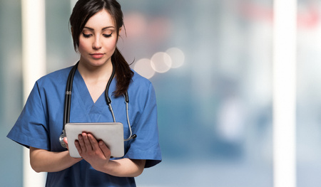 Portrait of a nurse using a digital tablet. Large copy-space