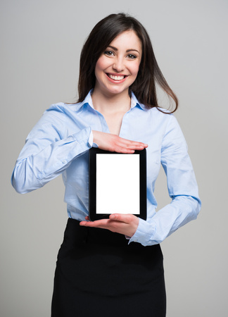 executive woman: Smiling young woman holding a tablet