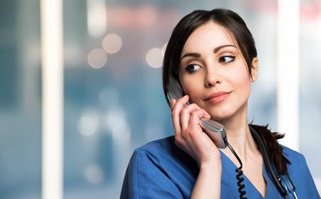 Portret van een glimlachende verpleegster die op de telefoon spreekt