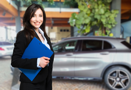 Saleswoman with folder and auto show background